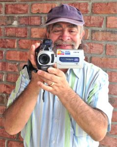 Edgard Bernal holding a video camera pointed at viewer